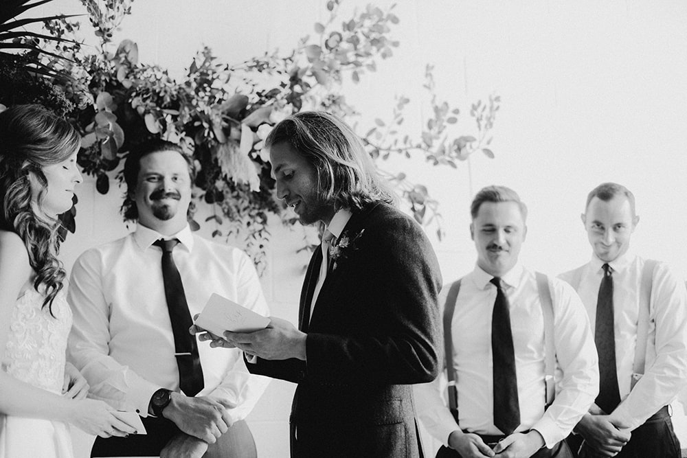 groom reading his vows in black and white photo