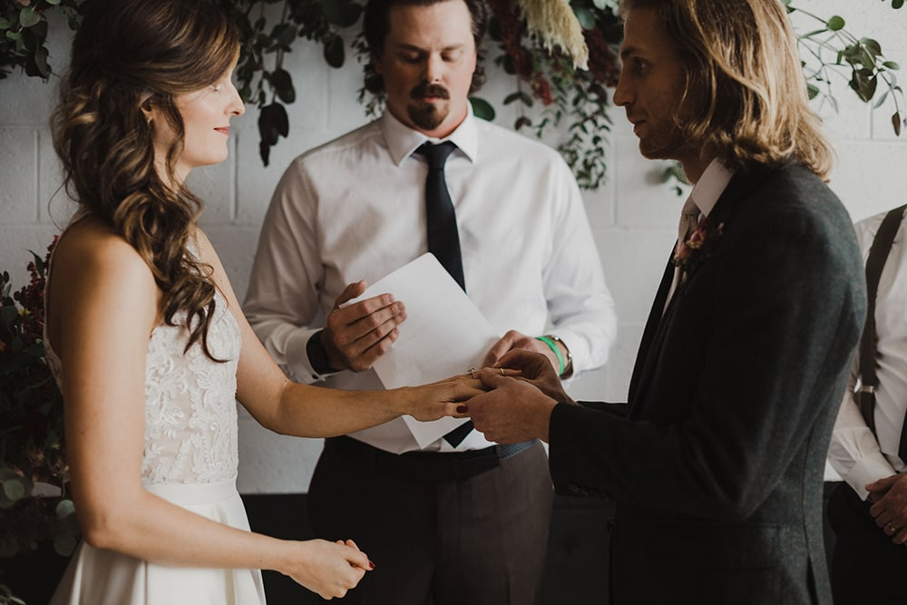 groom putting bride's ring on for the first time