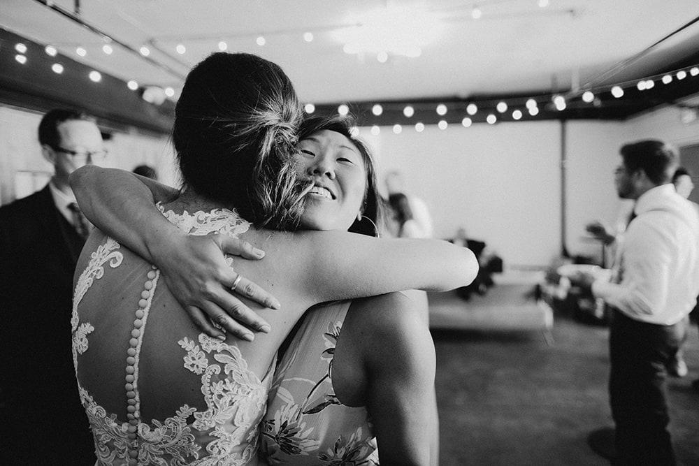 guest hugging bride after wedding