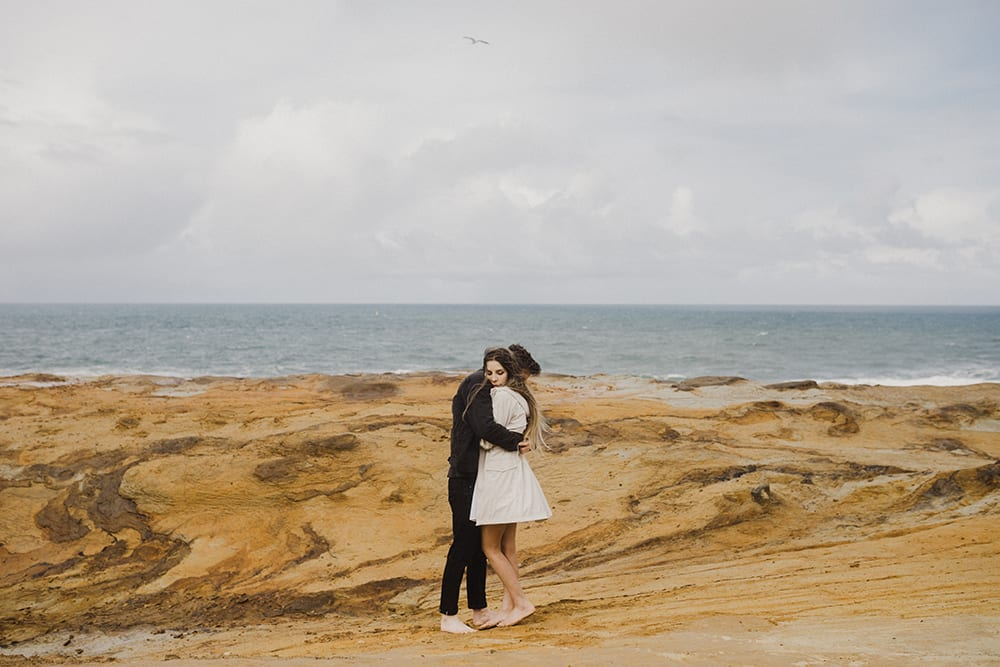 couple cuddling in dramatic ocean view