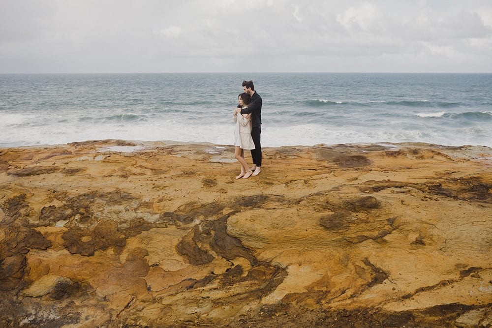 man and woman with ocean view behind them