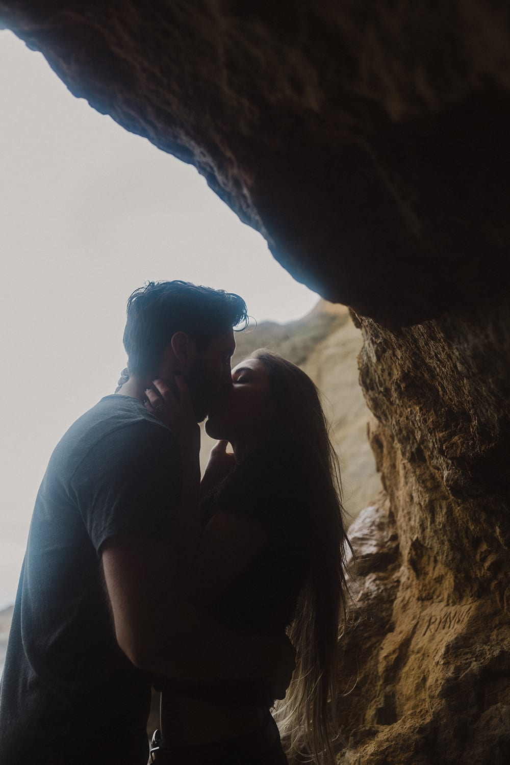 couple kissing in cave with dark lighting