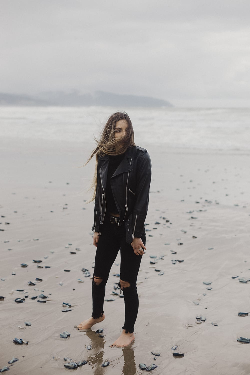 girl walking on beach with hair blowing