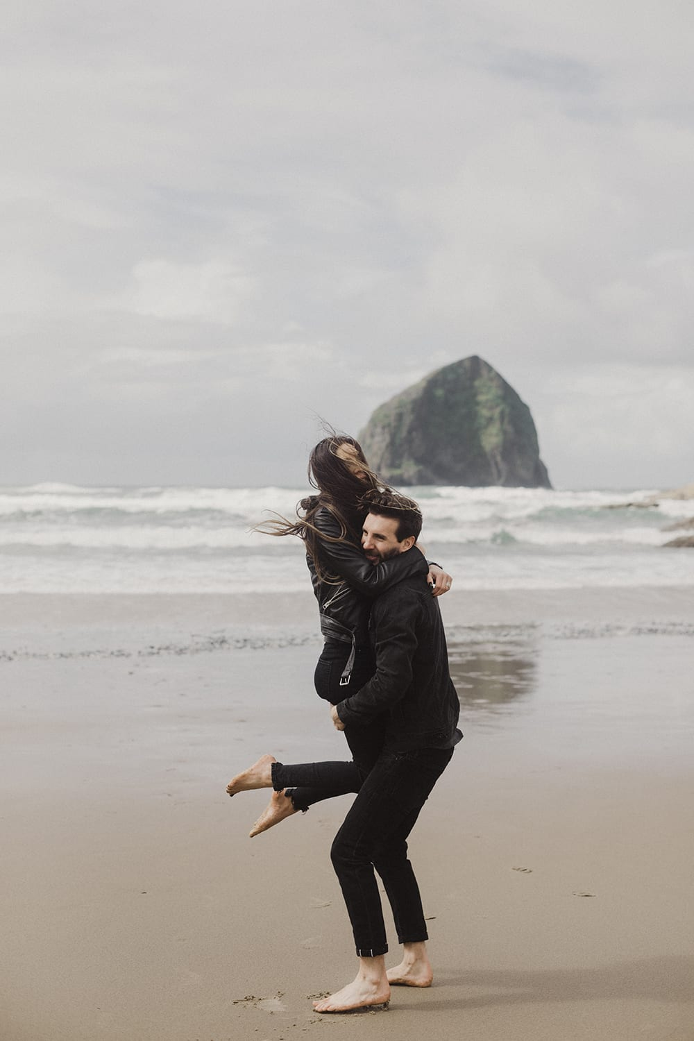 guy grabbing girl next to ocean with haystack rocks in backdrop