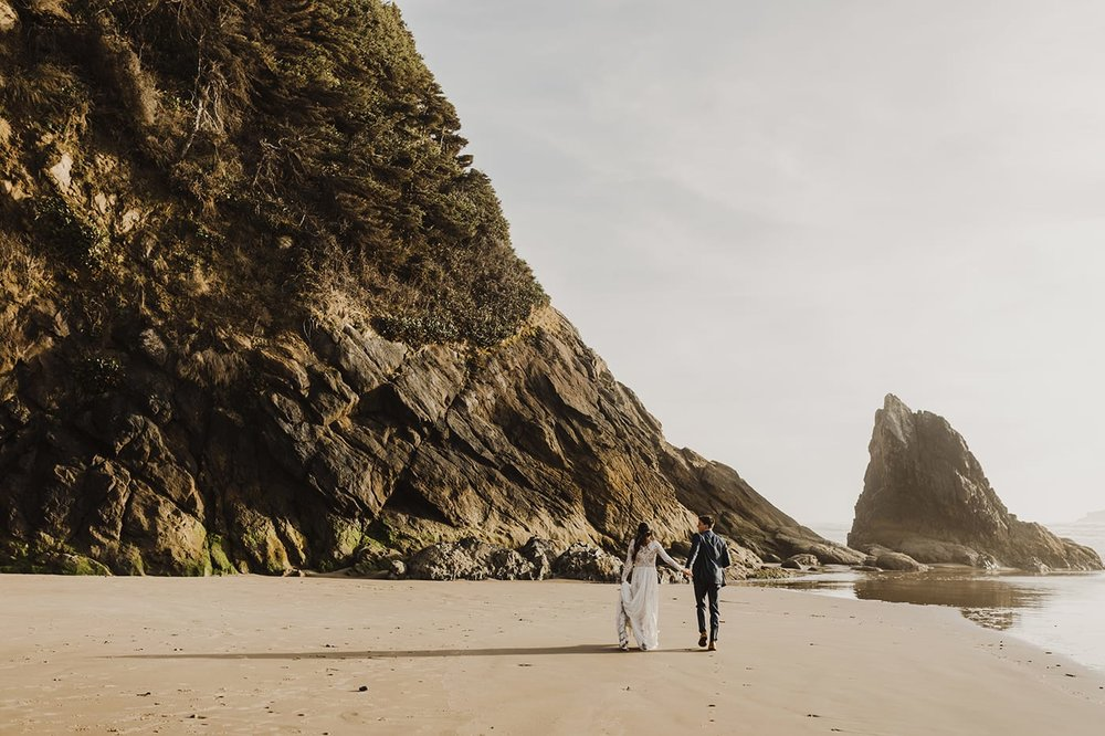 landscape view of bride and groom running toward cliffs on beach