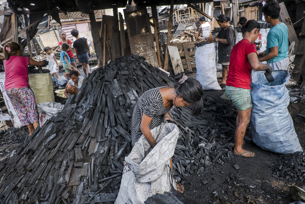 "After approximately 2 weeks of ""cooking"" the coal is ready to be packed and sold. Women and girls form the community pack them first to the big bags and than mater to the smaller bags that are directly sold in the community or to the big market in the center of Malabon. Malabon, Philippines, 2017"