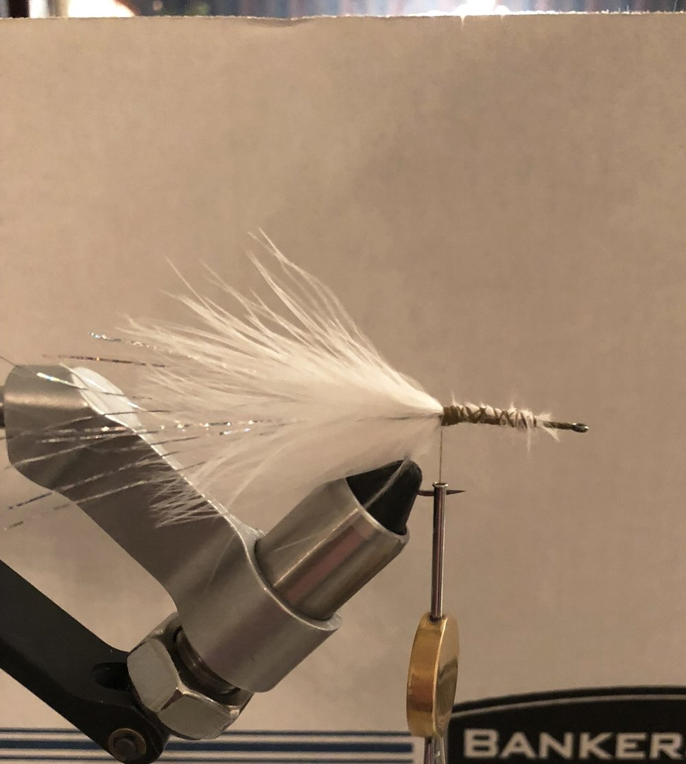 "Steps 1-3:  Place a size 6 Gamakatsu Stinger hook in the vise and make thread wraps from the eye to the bend of the hook. Tie in a small plume of marabou at the bend, then take 4 or five strands of flashabou and tie them in on each side of the fly at the bend of the hook, making sure the flash is slightly longer than the marabou. Then ""stack"" one more small plume of marabou on top at the bend of the hook. You can take thread wraps up and down the hook to make a body with the marabou you tied in. Your goal is to make a baitfish profile (fan shaped tail, body that gradually gets bigger towards the head.)"