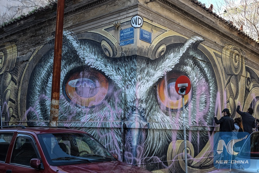 "Photo taken on Feb. 11, 2017 shows restorers from Street Art Conservators Group St.A.Co are repairing destroyed owl graffiti ""Knowledge Speaks-Wisdom Listens"" in Metaxourgeio district, central Athens. (Xinhua/Lefteris Partsalis)"