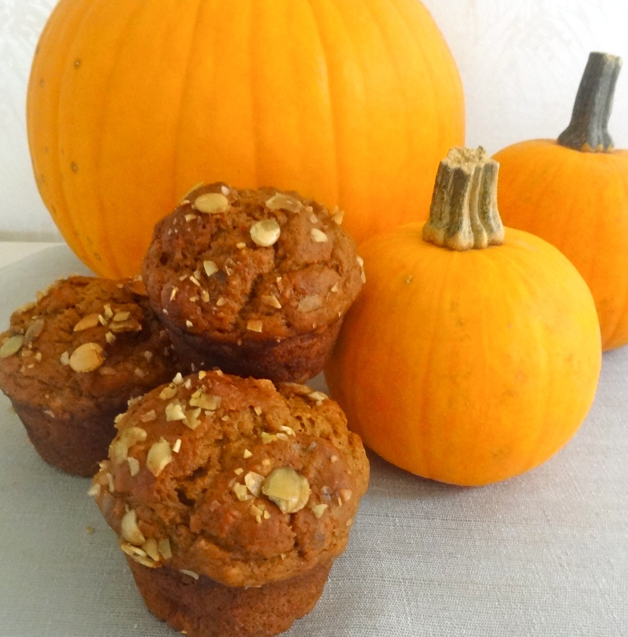 As soon as I see that pumpkins have replaced the corn and tomatoes at the market I start hungering for food that's autumn-like. Mostly pumpkin bread and muffins to snack on when I need a little something in the late afternoon with my last cup of coffee for the day.  I don't make pumpkin muffins as often as I do banana bread, but almost. This is my latest version, which has kefir because I happened to have some in the fridge. But buttermilk is fine too.  Reheat leftovers in a toaster oven for a few minutes if you need a quick breakfast.  Btw, I used to bake and mash the pumpkin insides to get the puree, but most of the time I use canned pumpkin or squash. NOT pumpkin pie mix. I want to mix in the spices of my choice, not theirs.   Pumpkin Muffins with Kefir and Pumpkin Seeds   3  tablespoons butter 1-3/4 cups flour 1 teaspoon baking soda 1/2 teaspoon baking powder 1/2 teaspoon salt 1 teaspoon cinnamon 1 teaspoon freshly grated nutmeg 1/8 teaspoon ground cloves 2 tablespoons brown sugar 1 cup mashed pumpkin (not pumpkin pie mix) 3/4 cup kefir 1/4 cup molasses 1 large egg 2-3 tablespoons crushed pumpkin seeds     Preheat the oven to 400 degrees. Lightly grease 9 muffin tin cups. Melt the butter and set it aside to cool. Sift together the flour, baking soda, baking powder, salt, cinnamon, nutmeg, cloves and brown sugar. In a separate bowl, combine the pumpkin, kefir, molasses, egg and cooled, melted butter. Add the liquid ingredients to the dry ones and mix only long enough to combine. Spoon the batter into the prepared muffin tin cups. Scatter the pumpkin seeds evenly on top of each muffin. Bake for 22-25 minutes or until a cake tester inserted into the center comes out clean. Makes 9
