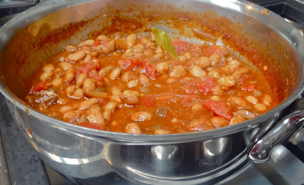 "I used to cook chili a lot more often than I do these days. I suppose I overdid it and Ed said ""HALT!"" on the chili and that was that for a while. But it's chili season isn't it? Maybe it's time to start the cycle again.  I have plenty of recipes that I've tried over the years but this one is my favorite. It's extra delicious with a blob of guacamole on top. Chili Con Carne 1-1/2 tablespoons vegetable oil 1 large onion, chopped 2 cloves garlic, minced 1 pound chopped or diced beef 28-ounce can Italian style plum tomatoes, drained and chopped 6-ounce can tomato paste 1-3/4 cups beef stock 2 tablespoons chili powder 2 teaspoons dried oregano 1-1/2 teaspoons ground cumin 1/2 teaspoon crushed red pepper 1/2 teaspoon freshly ground black pepper salt to taste 2 bay leaves 15-ounce can white beans, drained   Heat the vegetable oil in a large, deep sauté pan. Add the onion and garlic and cook over medium heat for 3-4 minutes or until the vegetables have softened. Add the meat and cook for 5-6 minutes or until the meat turns brown. Add the tomatoes, tomato paste, beef stock, chili powder, oregano, cumin, crushed red pepper, black pepper, salt and bay leaves. Bring the mixture to a boil, lower the heat, and simmer for 25 minutes. Add the beans and cook for another 15-20 minutes, or until most of the liquid has evaporated and the meat is surrounded by sauce as thick as gravy.   Makes 4 servings"