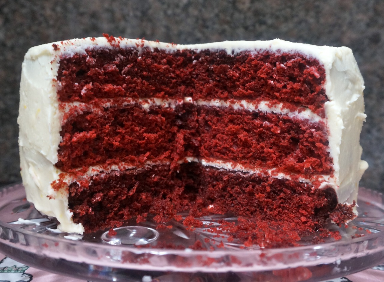 Last week a New York Times article bemoaned the fate of Red Velvet, which, like so many other American products, got twisted and turned and commercialized beyond repair and has been reproduced in so many gimmicky ways — red velvet candles, red velvet body mist, and so on — that it has become preposterous.   We've all seen this happen before. When something, anything is popular, there are going to be those who want to cash in on it in ways never intended.   They can sell it, but of course we don't have to buy it. And if we don't buy it, they will stop selling it and we can move on.   But that doesn't mean that the original product was outlandish. There is a reason that Red Velvet Cake has endured. People love how it tastes. It has a miraculously soft texture. In its article, the New York Times, while ridiculing the commercialization, deemed Red Velvet Cake a classic.   Truth to tell, I never understood the wow in the whole red velvet cake thing. To me the versions I tasted seemed as if they couldn't make up their minds about whether to be a vanilla cake with too much color and too-little cocoa to make a flavor difference or a devil's-food cake.   But after experimenting somewhat with recipes, I came up with one that's mighty good! So, now I get it. It isn't vanilla cake. Or devil's-food. Or chocolate cake. It's its own thing. A classic. Here's the recipe, plus a recipe for frosting that's way less sweet than most:       Red Velvet Cake    3-1/2 cups all-purpose flour 1/3 cup cocoa powder (not Dutch process) 1 teaspoon salt 2 cups sugar 1-1/2 cups vegetable oil 3 large eggs, at room temperature 1 ounce red food coloring mixed with 6 tablespoons water 1-1/2 teaspoons vanilla extract 1-1/4 cups plain yogurt 2 teaspoons baking soda 2 teaspoons white vinegar Lemon-Cream Cheese Frosting       Preheat the oven to 350 degrees. Lightly grease 3 9-inch cake pans. Sift the flour, cocoa powder and salt into a bowl and set aside. Beat the sugar and vegetable oil together at medium speed for 1-2 minutes or until thoroughly blended. Add the eggs, one at a time, beating after each addition. Add the food coloring mixture and vanilla extract and stir the ingredients at low speed until thoroughly blended. Add the flour mixture, alternating with the yogurt, beating the ingredients after each addition. Mix the baking soda and vinegar in a small bowl, pour it into the batter and blend it in thoroughly. Spoon the batter equally among the cake pans. Bake for about 30-35 minutes or until a cake tester inserted in the center comes out clean. Let the cake layers cool for about 10 minutes, then insert them onto a cake rack to cool completely. Before serving, frost the cake.     Lemon-Cream Cheese Frosting      1 pound cream cheese at room temperature 1/2 cup butter at room temperature 2 cups confectioner sugar  1 tablespoon lemon juice  1 teaspoon vanilla extract 1 teaspoon grated fresh lemon peel     Beat the cream cheese, butter, confectioners sugar, lemon juice, vanilla extract and lemon peel together at low-medium speed until smooth, creamy and well blended.    Makes 10-12 servings