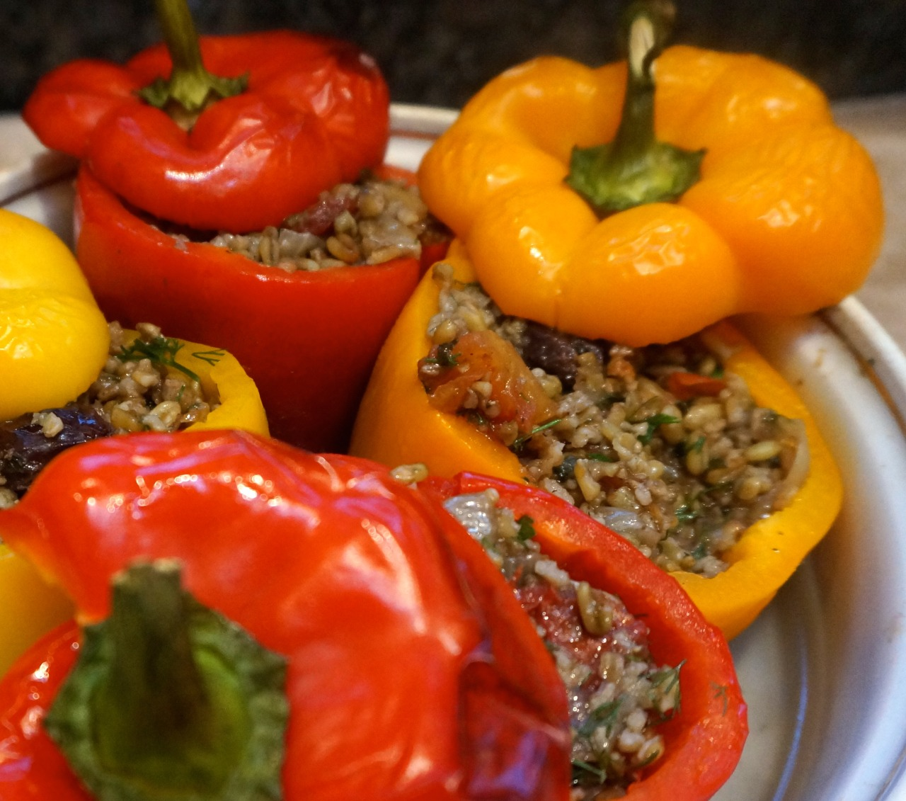 It's been a long long time since I ate stuffed peppers and a long time since I cooked them. Bell peppers and my tummy don't always get along. But I decided to give them another try. My grandmother made a dish something like this one, only she used rice as the base. I switched to freekeh instead because I love this particular grain. It worked beautifully. Looks good, tastes good, perfect for when you need a make-ahead dish to pop in the oven for dinner. Perfect for Sukkot, when stuffed foods are traditional. Easily transportable too. Turkish Stuffed Peppers   8 bell peppers 1 cup cracked freekeh (or use rice) 2 tablespoons currants (or raisins) 5 tablespoons olive oil 2 medium onions, chopped 2 tablespoons pine nuts, optional salt and freshly ground black pepper to taste 1 large tomato, chopped 2 teaspoons sugar 1 teaspoon ground allspice 1-3/4 cups vegetable stock 2 tablespoons chopped fresh parsley 2 tablespoons chopped fresh dill 1 tablespoon chopped fresh mint 2 tablespoons lemon juice   Place the peppers in a deep bowl and pour boiling water over them. Weight them down to keep them under the water. Let rest for 5 minutes. Drain and repeat the process with cold water. Cut a lid from the top of the peppers, but reserve the lids. Scoop out and discard the seeds and membranes. Set the peppers aside. Place the freekeh and currants in a bowl and pour boiling water over them. Let rest for 30 minutes. Drain. Heat the olive oil in a sauté pan over medium heat. Add the onions and pignoli nuts, if used, and cook, stirring occasionally, for 4-5 minutes or until the onion has softened and is slightly golden. Add the freekeh and currants and some salt and pepper to taste. Cook for another 1-2 minutes, stirring occasionally. Add the tomato, sugar and allspice and cook for another minute, stirring occasionally. Add the stock, bring to a boil, cover the pan and lower the heat. Cook for about 40 minutes or until the freekeh is soft and all the liquid has been absorbed. Remove the pan from the heat. Stir in the parsley, dill, mint and lemon juice. Let cool. Use to fill the peppers. Place lids on top. (You may prepare to this point and cook later). Preheat the oven to 350 degrees. Place the peppers in a baking dish. Add 2 cups of water to the dish. Bake the peppers for 40 minutes. Let cool slightly before serving (warm or at room temperature).   Makes 8 servings