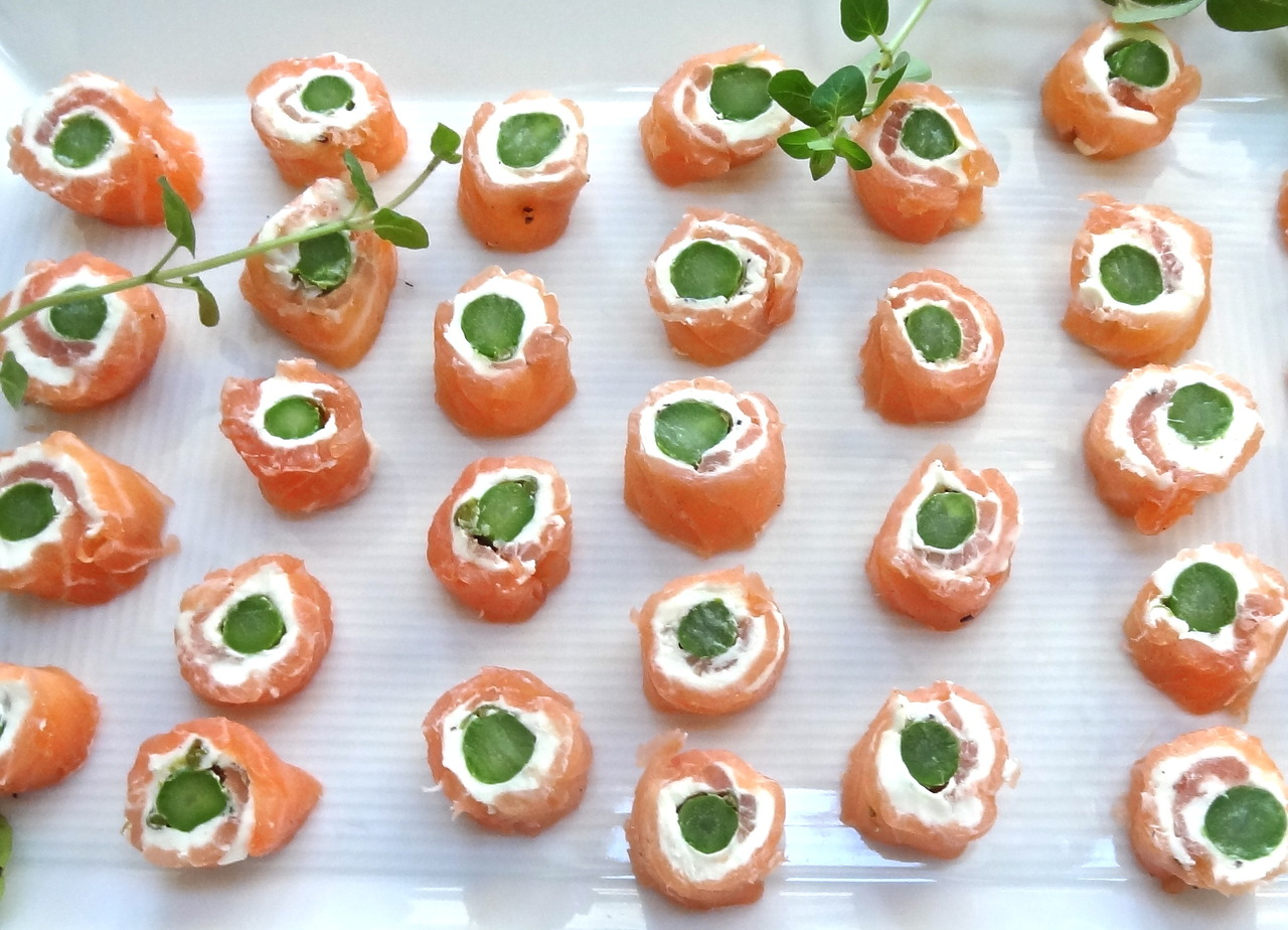 "What's a good last minute, easy hors d'oeuvre?   This one!   My neighbor asked a few of us women over the other night because one of the women on the block is moving. And when I asked if I could bring something she said ""yes, how about some hors d'oeuvre!""   I didn't have much time, so I prepared an old standby: smoked salmon rolls.    No recipe really. Here's what you do: buy some smoked salmon (ask them to slice it wide, not into narrow strips). Wipe each slice with paper towels (so you can spread the cheese). Then spread some cream cheese (goat cheese, herb cheese or anything else spreadable) on the top of each slice. Place a cooked asparagus (or green string bean) on top. Sprinkle with lemon juice and freshly ground black pepper (add chives or capers if you wish) and roll the salmon slices, jelly roll style.    After you roll the slices, place them seam side down on a dish and refrigerate for about one hour (to firm up the cheese). Then, slice each roll into bite size hors d'oeuvre.   It couldn't be easier. And they look good too."