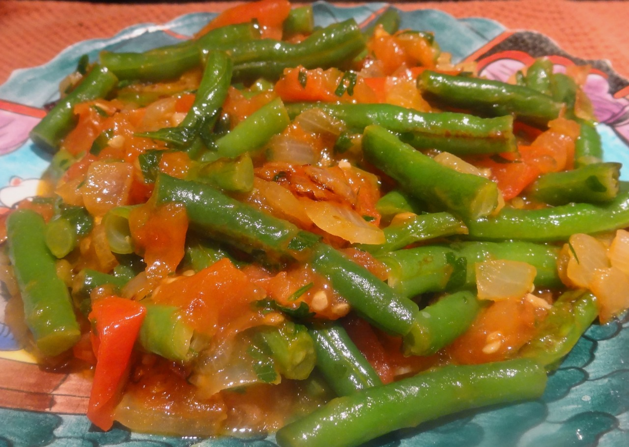 When my husband Ed asks for seconds on a vegetable side dish I know I've got a good recipe. The other evening I cooked this string bean and tomato dish. We are so used to eating crispy, tender-but-still-firm vegetables that this dish, with its softer side, was a surprise wonder. Not that the vegetables are soft and mushy like people used to make them (I have a cookbook from the 1930s that instructed the reader to cook string beans for 45 minutes!). But they are not crunchy either. I served this with chicken, but it could be a good part of a vegetarian meal or a meatless Monday meal. It would go well with mashed potatoes and roasted cauliflower or cooked egg noodles, polenta, mushroom ragout and such. It would also be a good accompaniment to scrambled eggs.   String Beans with Tomatoes   1 pound green string beans 1/4 cup olive oil 1 medium onion, chopped 2 cloves garlic, chopped 2 medium tomatoes, or 4 plum tomatoes, chopped 1/4 cup chopped fresh parsley salt to taste 1/2 teaspoon sugar 1/8 teaspoon cayenne pepper 2 tablespoons lemon juice   Rinse the string beans, cut the ends off and cut the beans into 1-1/2 to 2-inch pieces. Heat the olive oil in a sauté pan over medium heat. Add the onion and green beans and cook for 3 minutes, stirring occasionally. Add the garlic and cook briefly. Cover the pan and cook for 3-4 minutes or until the beans are almost tender. Add the tomatoes, parsley, salt and sugar and stir the ingredients to mix them evenly. Sprinkle with the cayenne pepper. Cover and cook for another 3-4 minutes or until the vegetables are soft. Sprinkle with the lemon juice. Makes 4 servings