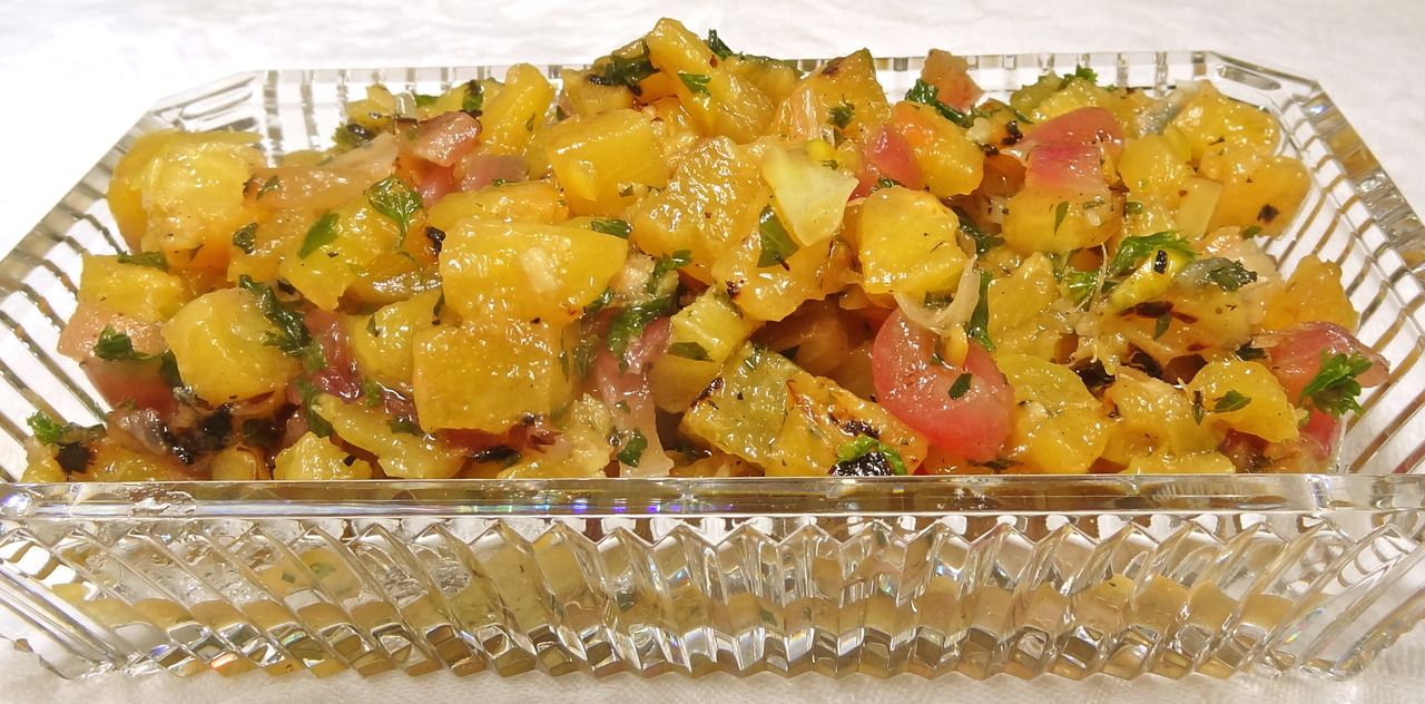 Remember that one chili pepper I was able to grow in my garden? Well, I don't have much of a green thumb, but I did get a few more peppers this week, so I had to figure out ways to use them. I came up with this grilled pineapple salsa. I used it as a side dish for some grilled fish I made for dinner. This salsa is just a bit hot and also is tangy (from the lime juice) and sweet, not just because of the honey, but also because grilling fruit brings out the sugars. And I have to add, that grilled pineapple tastes somewhat like rum, which is never a bad thing. Grilled Pineapple Salsa 1/2 large pineapple, skin removed, cut into 1/2-inch thick slices 1 small red onion, peeled, cut into 1/2-inch thick slices 3 tablespoons vegetable oil 2 small chopped chili peppers (such as serrano), deseeded and chopped 2 tablespoons chopped flat leaf parsley 2 tablespoons chopped fresh mint 2 teaspoons chopped fresh ginger 2 tablespoons lime juice 1 tablespoon honey 1/2 teaspoon ground cumin Preheat an outdoor grill (or use a grill pan). Brush the the pineapple and onion slices with some of the vegetable oil. Grill the slices for 2-3 minutes per side or until browned and softened. Remove the slices, chop them into small pieces and place them in a bowl (discard the hard fibrous pineapple core). Add the peppers, parsley, mint, ginger, lime juice, honey and cumin and toss ingredients to distribute the ingredients evenly. Let rest at least 15 minutes before serving. Good with fish. Makes about 2 cups