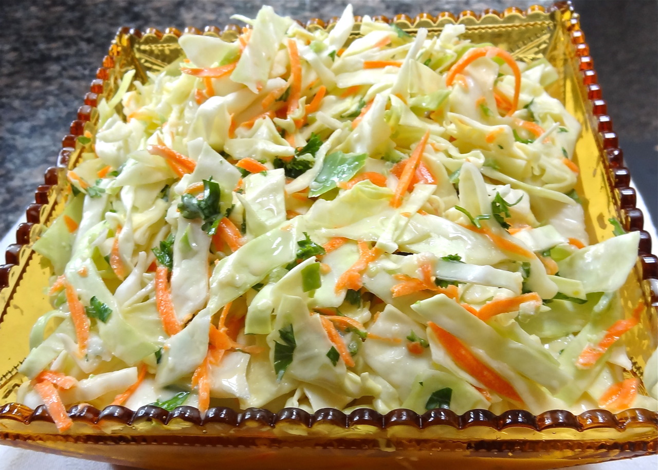 An American summer calls for Cole Slaw. Which is very funny when you come to think of it because Cole Slaw is basically a Dutch dish (recipes brought to the Americas in colonial times with the Dutch settlers). But, Dutch origin or not, this is a dish you can find at delis everywhere across the country. The stuff of summer picnics and July 4th celebrations and weekend barbecues on the deck. Even my Romanian-Jewish grandmother made Cole Slaw (hand grated, before the days of the food processor). I have a zillion Cole Slaw recipes. Well, not really a zillion, but a lot. Like I said yesterday about potato salad, I could write an entire book about this stuff. I always tinker with a Cole Slaw recipe and then, voila! I have a whole new recipe. Like this dairy version that has buttermilk in it. The buttermilk (which you can use to make a smoothie or make biscuits or the best pancakes you ever tasted) gives this Cole Slaw version a nice tangy taste, which is refreshing in the hot weather. We've had some of that already, at least here in the east. This week I felt confused that it was still May but felt like July outside. Btw, I usually shred the cabbage by hand with my big chef's knife. I like the chunkier pieces you get this way. However, I use the processor (shredding blade) for the carrots and the s-blade for the parsley. Buttermilk Cole Slaw 6 cups shredded cabbage (about 1-1/4 pounds) 2-3 shredded carrots 1 small grated onion, optional 2-3 tablespoons chopped fresh parsley 2 tablespoons chopped fresh dill, tarragon or savory, optional 1-1/3 cups buttermilk 1/3 cup mayonnaise 2-3 tablespoons cider vinegar 1 teaspoon salt or to taste pinch or two cayenne pepper Place the cabbage, carrots, onion, if used, parsley and herb, if used, in a large bowl and toss to distribute the ingredients evenly. In another bowl, whisk the buttermilk, mayonnaise and 2 tablespoons of the vinegar and pour over the vegetables. Toss ingredients, sprinkle with salt and cayenne pepper and let rest for at least 15 minutes before serving. Taste for seasoning, and add the remaining vinegar for more tang, and some salt and cayenne pepper if needed. Makes 8 servings