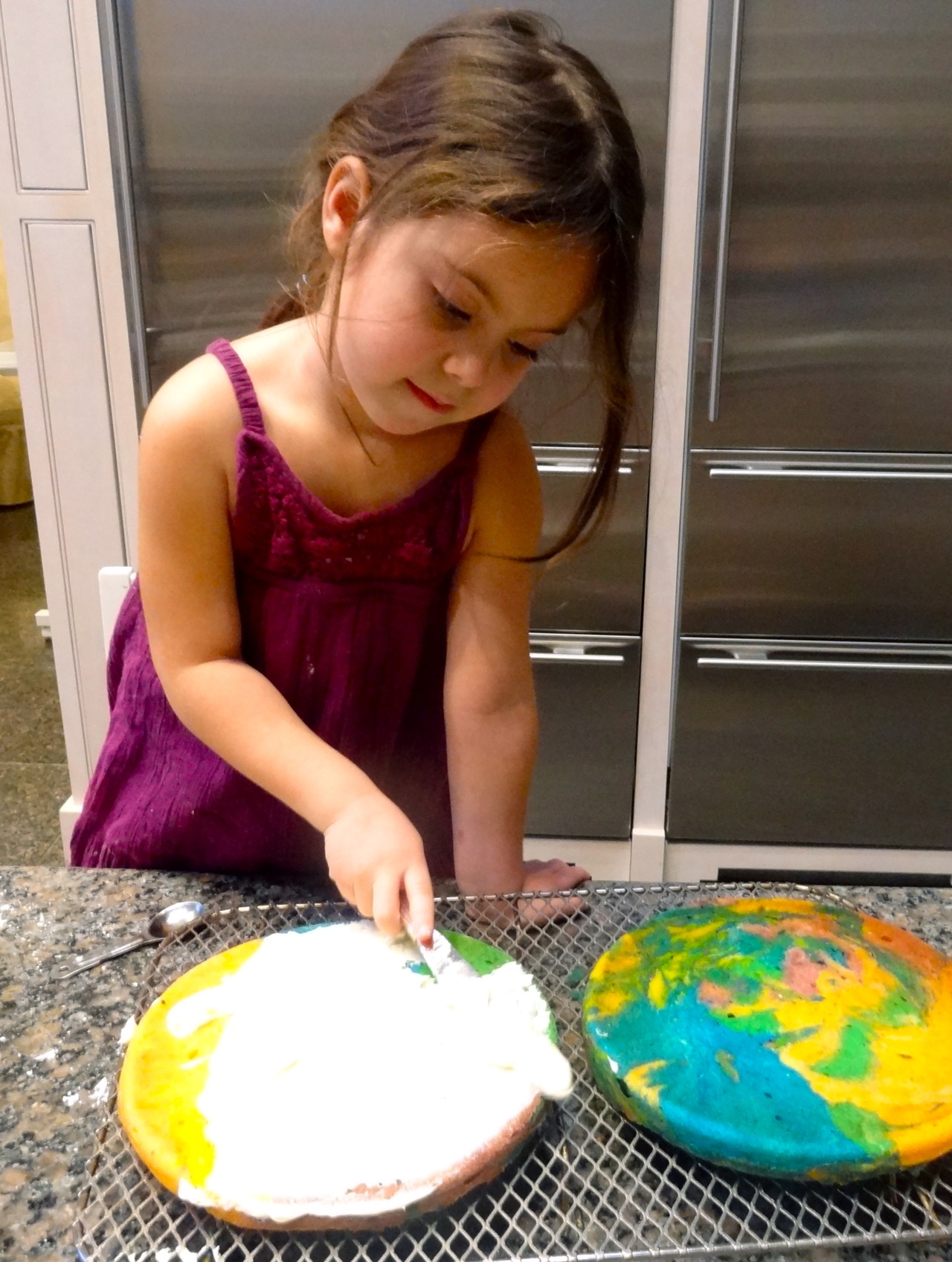 "Saturday may be St. Patrick's Day, but for me the important milestone that day is my grand daughter Nina's 5th birthday. She always asks me to bake a birthday cake for her and when she came to my house a few weeks ago we discussed what she would like and she told me ""a rainbow cake with vanilla."" Which is what we made for practice, just to see if that's what she really wanted. We were able to have all these good colors thanks to several squirts of food coloring, which I added to small bowls of yellow cake batter and let Nina mix.  Here she is frosting her practice cake with a cream-cheese frosting. Her real birthday cake will have the same frosting plus an Ariel, Little Mermaid design on the top. And a Little Mermaid Candle. Of course. Cream Cheese Frosting for Yellow Cake Cream Cheese Frosting: 3/4 cup butter at room temperature 12 ounces cream cheese at room temperature 1-1/2 cups confectioner's sugar 1-2 teaspoons vanilla extract Beat the butter, cream cheese and confectioner's sugar together until smooth and creamy. Add 1-2 teaspoons vanilla extract, enough to make the frosting easy to spread. Enough for one 9-inch layer cake"