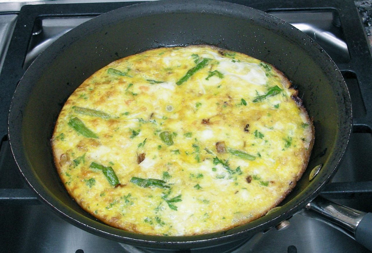 When I'm developing recipes for an article I'm writing I need to experiment, so my family gets to be the guinea pigs (also my neighbors and friends and sometimes any repairman who happens to be in the house). This past weekend, being Mother's Day and all, my children and grandchildren were here so I tried this frittata recipe on them and it got good reviews. It makes a good hors d'oeuvre if you cut it into slim slices, but can also be a good vegetarian dinner item. I like it hot but it's also good at room temperature and even cold. Asparagus and Feta Frittata 12 medium asparagus spears 2 tablespoons olive oil 1 medium onion, chopped 8 large eggs, beaten 2 tablespoons milk 2-3 tablespoons chopped fresh parsley 2 tablespoons butter 1 cup crumbled feta cheese 1/4 cup grated Parmesan cheese freshly ground black pepper to taste Preheat the oven broiler with the rack about 6-inches from the heat. Cut the tips from the asparagus and set them aside. Cut the remaining part of the spear into 2-inch chunks and set aside. Heat the olive oil in a large saute pan over medium heat. Add the onion and cut asparagus spears and cook for about 2 minutes. Add the asparagus tips and cook for another minute. Remove the vegetables and set aside. Mix the eggs, milk and parsley in a bowl. Heat the butter in the saute pan. When the butter has melted and looks foamy, return the vegetables to the pan. Scatter the feta and Parmesan cheeses on top. Pour in the egg mixture and turn the heat to low. Stir once or twice then cook undisturbed for about 8 minutes or until the bottom has set and is golden brown. Place the pan under the broiler and cook for up to a minute or until the top of the frittata is puffed and golden. Season to taste with black pepper. Makes 4 servings