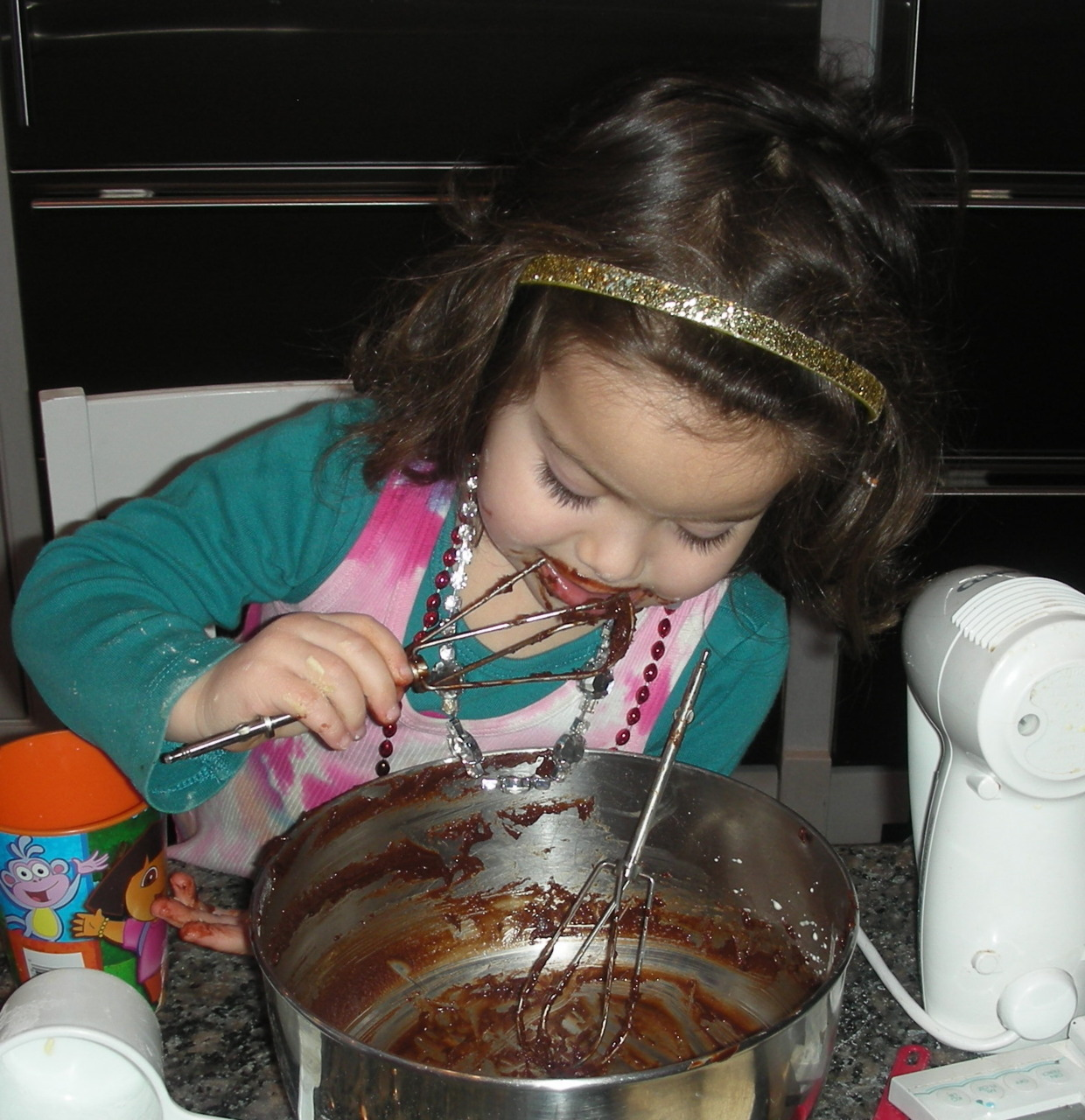 School's out. Make brownies. If you have a kid or a grandkid, make brownies with the kid or grandkid. That way you get delicious dessert, delicious photos and delicious memories. This picture shows my granddaughter Nina, almost 4, after making a batch of our favorite chocolate-chip brownies. Her brother and cousins weren't at my house so she had the beaters, spatula, wooden spoon and bowl all to herself. Check out the jewelry. She was wearing her finest plastic rubies, sapphires and diamonds. Here's the recipe; Chocolate Chip Brownies 4 ounces unsweetened chocolate 6 tablespoons unsalted butter 2 large eggs 1 cup sugar 3/4 cup all-purpose flour 3/4 teaspoon baking powder 1/2 teaspoon salt 1 teaspoon vanilla extract 1/2 cup semisweet chocolate chips Preheat the oven to 350 degrees. Lightly grease an 8-inch square baking pan. Put the chocolate and butter in the top part of a double boiler over barely simmering water. Cook, stirring occasionally, until the chocolate and butter have melted. Stir to blend the ingredients thoroughly. Remove the top part of the double boiler from the bottom pan and set it aside to cool. Combine the eggs and sugar in a mixing bowl and beat them with an electric beater set at medium speed for 2-3 minutes or until thick, light and well-blended. Add the flour, baking powder and salt and blend ingredients thoroughly. Stir in the vanilla extract. Add the chocolate-butter mixture and blend ingredients thoroughly. Stir in the chocolate chips. Spoon the batter into the prepared pan. Bake for 28 minutes or until a cake tester inserted into the center comes out clean. Cool the brownies in the pan. Cut into 16 squares. Makes 16