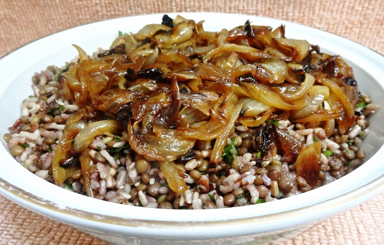 I think I could make Mujadarah in my sleep. Okay, maybe I haven't actually cooked it as often as challah or spinach pie or butter cookies, but this dish is a mainstay in the Fein household. I serve it when my kids come. Sometimes I make a small portion for just Ed and me. But mostly I serve it for buffet dinners, like when a grandchild is born and we have a welcome party. And it has become a permanent item for my Yom Kippur Break-the-fast. The first time I served Mujadarah at my Break-the-fast, people wondered what it was and took a little taste, then came back for more. Much more. The next year I doubled the amount I served. Mujadarah is a Middle Eastern specialty. This version has brown rice but you could substitute bulgur wheat. I make it well ahead of time, separately store the grains and onions in the fridge, then reheat them separately too. That makes it really easy for me when I have a lot of guests over. Brown Rice Mujadarah  1/2 cup olive oil 4 large yellow onions, peeled and sliced 1 cup brown rice 1 cup lentils water or stock 1/2 cup chopped fresh parsley salt to taste   Heat 4 tablespoons of the olive oil in a large sauté pan over low-medium heat. Add the onions and cook, stirring occasionally, for about 20 minutes or until the onions are soft and brown. Set aside. If not serving the dish immediately, spoon the onions into a container and cover the container. Refrigerate when cool. Place the rice in a saucepan, cover with 2 cups water or stock, bring to a boil, stir and cover the pan. Turn the heat to low and cook for about 30 minutes or until tender. Spoon the rice into a bowl. While the rice is cooking, place the lentils in a saucepan and cover with water or stock. Bring to a boil over high heat. Lower the heat, cover the pan and cook for about 25 minutes or until tender. Drain and set aside. Stir in the remaining 4 tablespoons olive oil. Add the parsley and toss the ingredients. Add salt to taste. If serving immediately, stir in the onions with any accumulated juices. If serving at a later time, stir in the onions and juices, cover the pan and reheat in a covered baking dish in a preheated 350 degree oven. Makes 4 servings