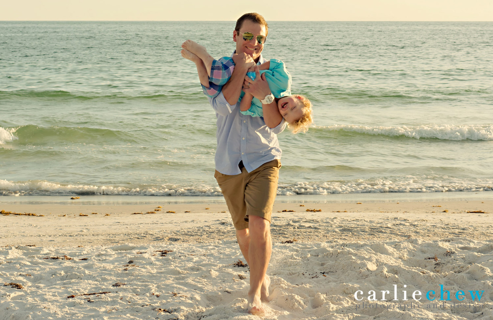 Father running with son in arms while being photographed by Carlie Chew Photography on Anna Maria Island.