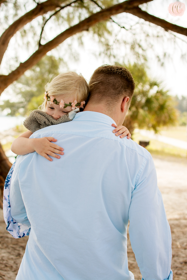 Little girl over Dad's shoulder at Sand Key Park in Clearwater with family photographer Carlie Chew Photography