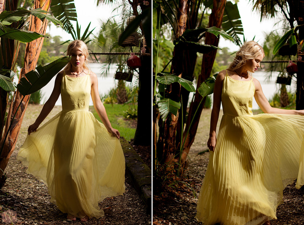 Model in front of tropical landscape in yellow blowing dress posing for fashion photographer Carlie Chew Photography in Tampa, Florida