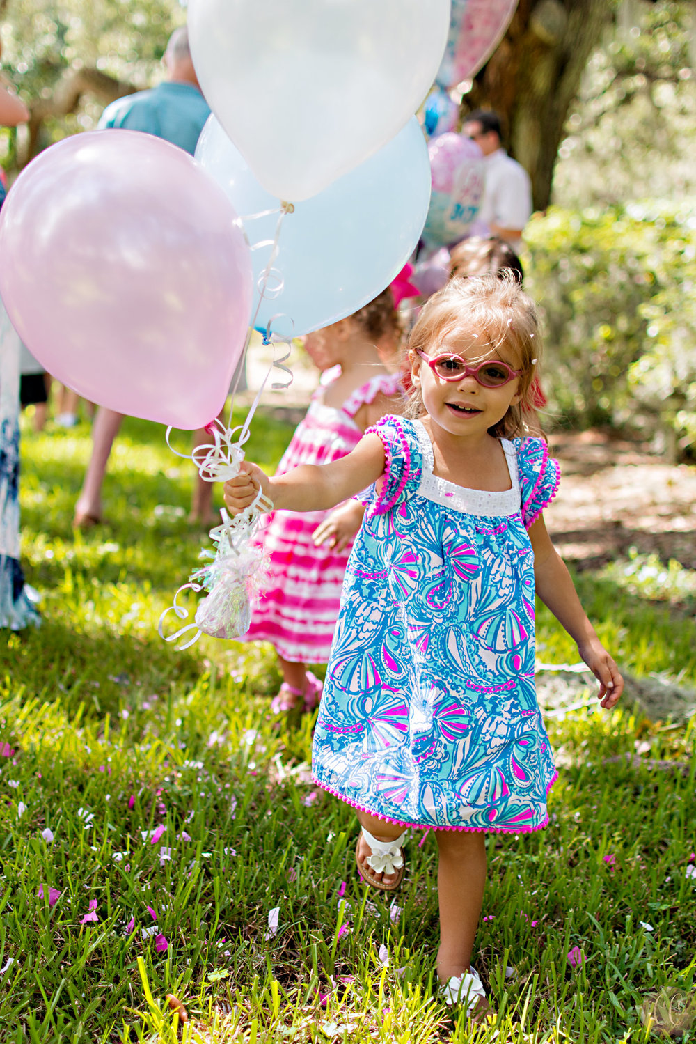 Big sister runs with balloons at her parents gender reveal party at The Tampa Yacht Club, photos taken by Carlie Chew Photography