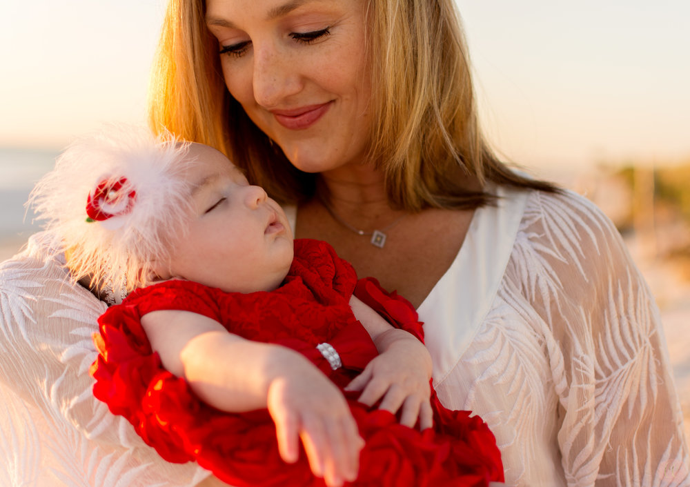 Mother poses with newborn baby in red dress for family photographer Carlie Chew Photography at Honeymoon Island in Dunedin, Florida