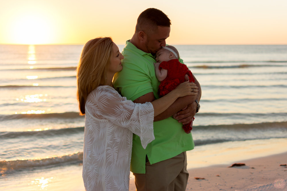 Couple poses with newborn baby for family photographer Carlie Chew Photography at Honeymoon Island in Dunedin, Florida