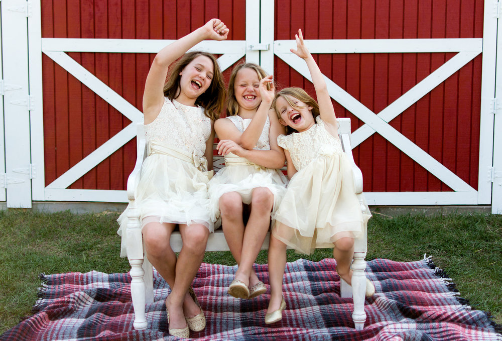 Girls having fun! Sister's laugh in photograph in front of barn taken in Dade City, Florida by Carlie Chew Photography