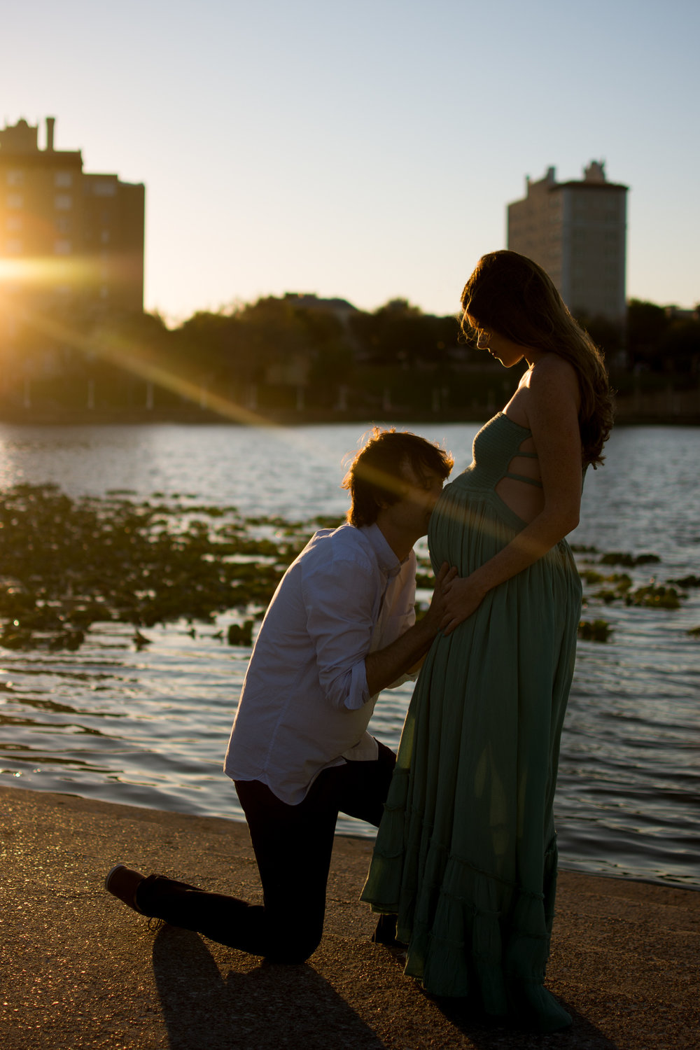 father kisses his wife's pregnant belly during a maternity shoot with Carlie Chew Photography at Mirror Lake, Lakeland, FL
