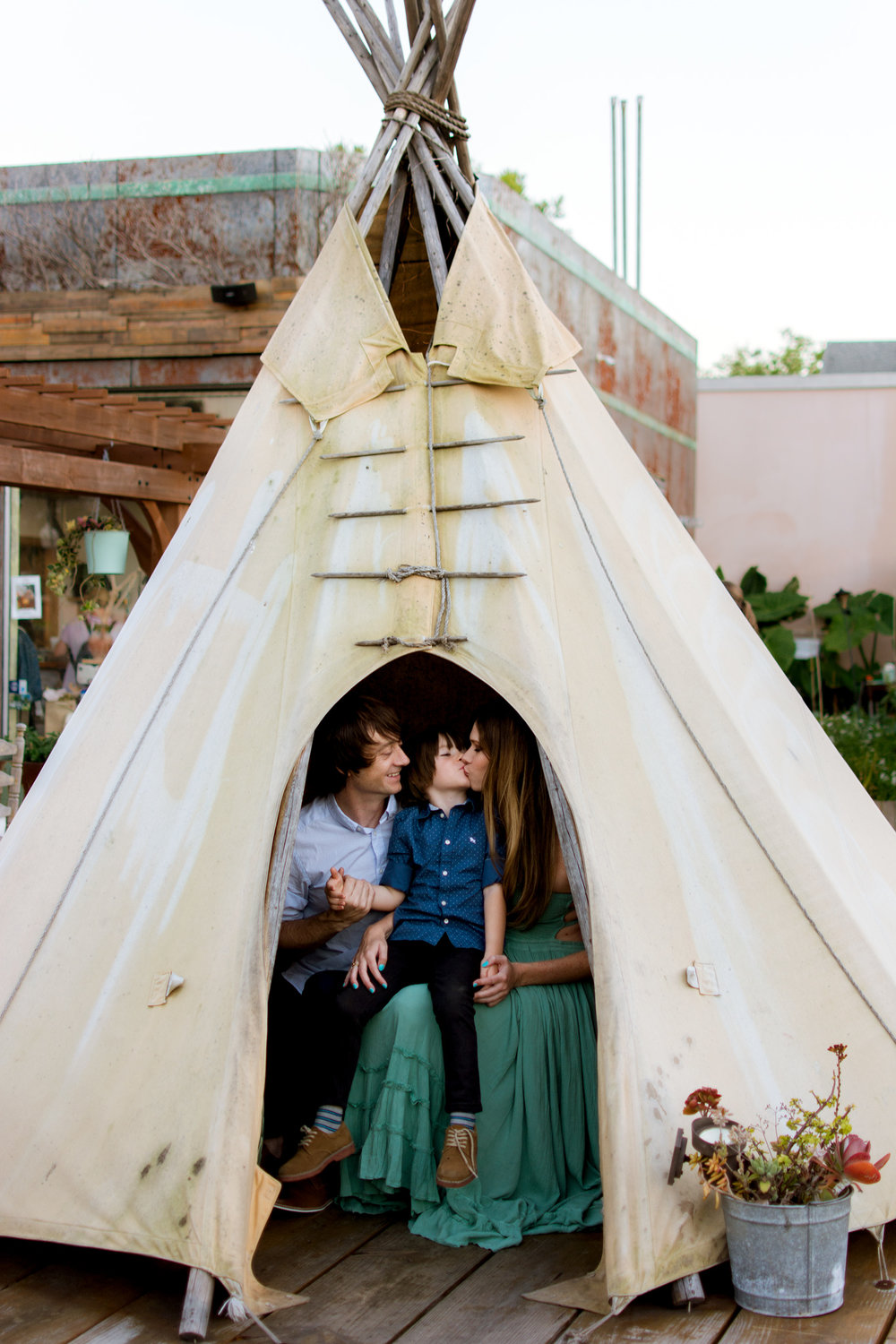 Mother kisses her son in a teepee during her maternity session with Carlie Chew Photography at the Poor Porker, Lakeland FL