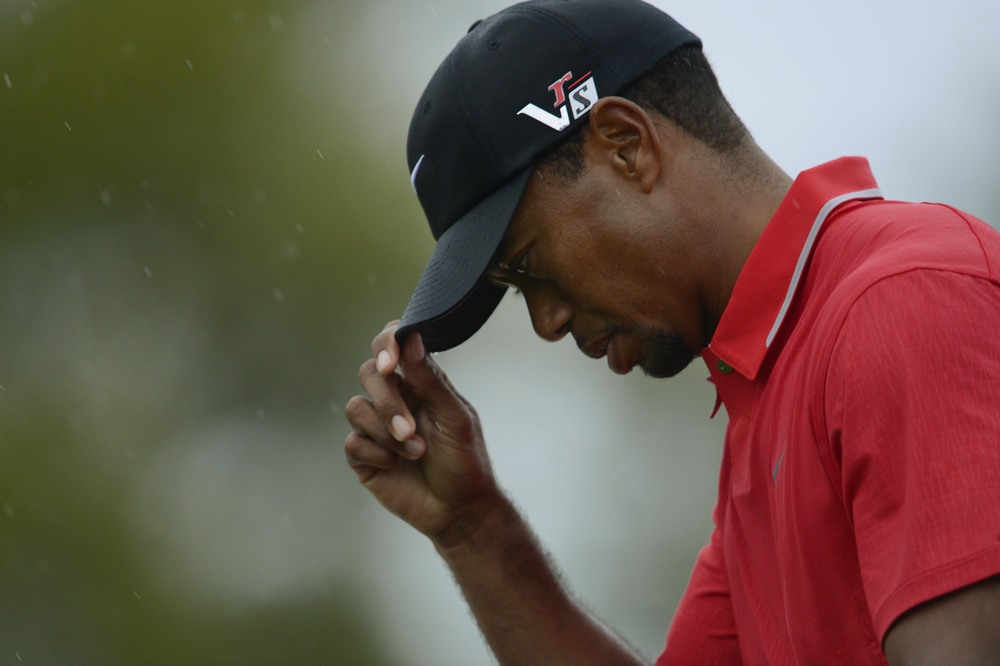 Tiger Woods tips his cap as he walks to the 18th green during the final round of the 2013 The Masters golf tournament at Augusta National Golf Club.