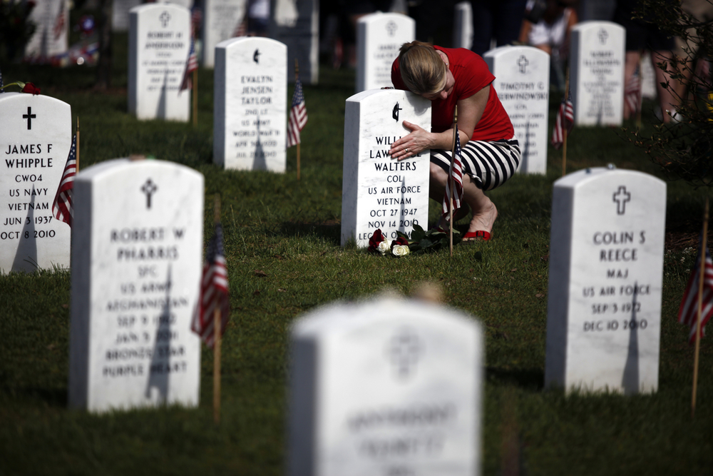 Sondra May of Mclean, Va. hugs the grave of her father Air Force Col. William Lawrence Walters at Section 60 of Arlington National Cemetery on Memorial Day, Monday, May 28, 2012.