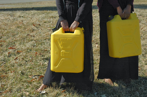 halima and anisa holding jerry can.JPG