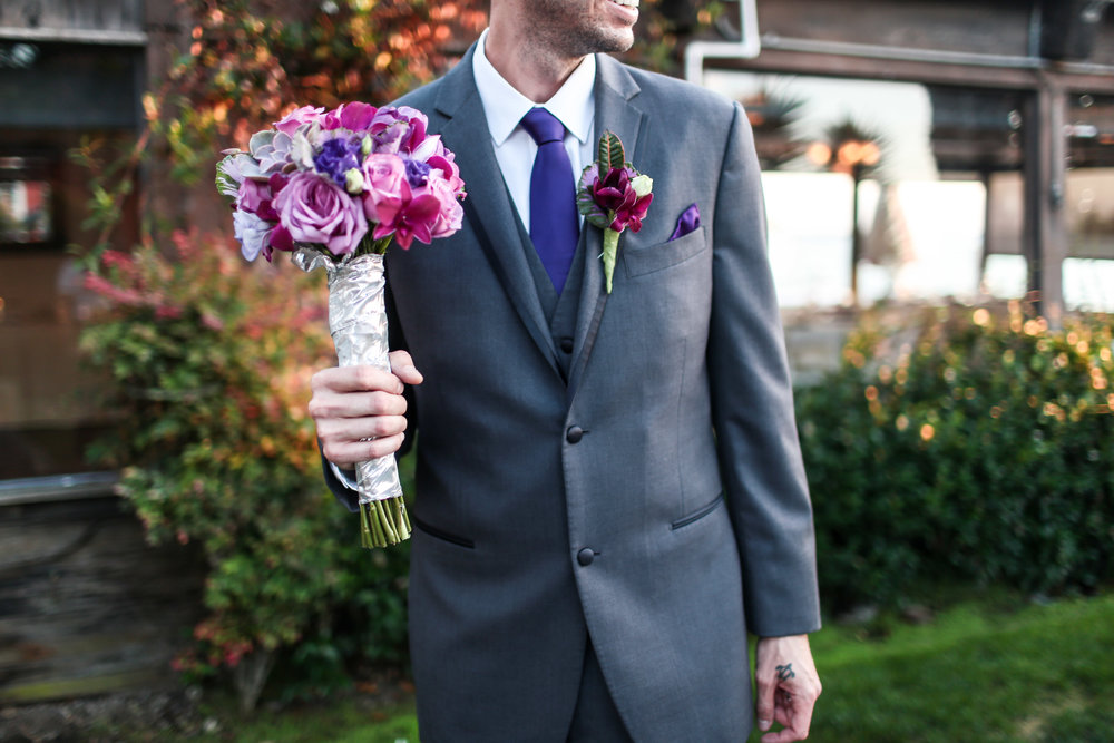 Eric holds his bride's bouquet.