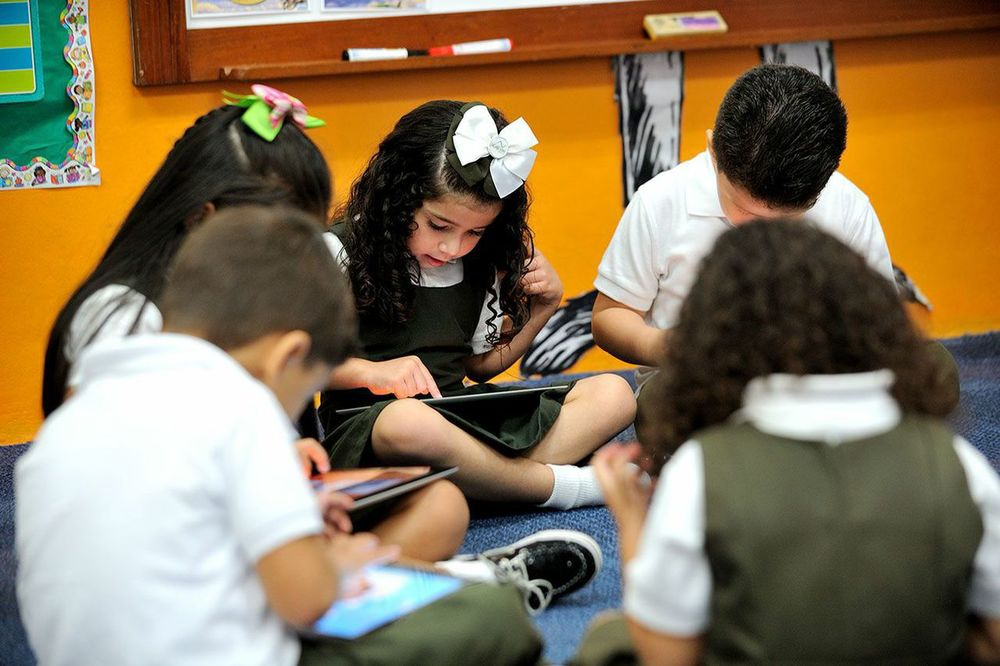 Pre-school students working on iPads.