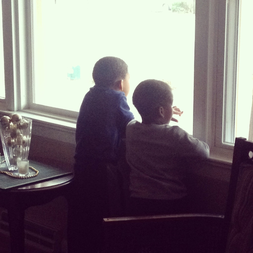 The house became too quiet, so I went to investigate. I found two little boys watching for Daddy Captain America to come home from work.