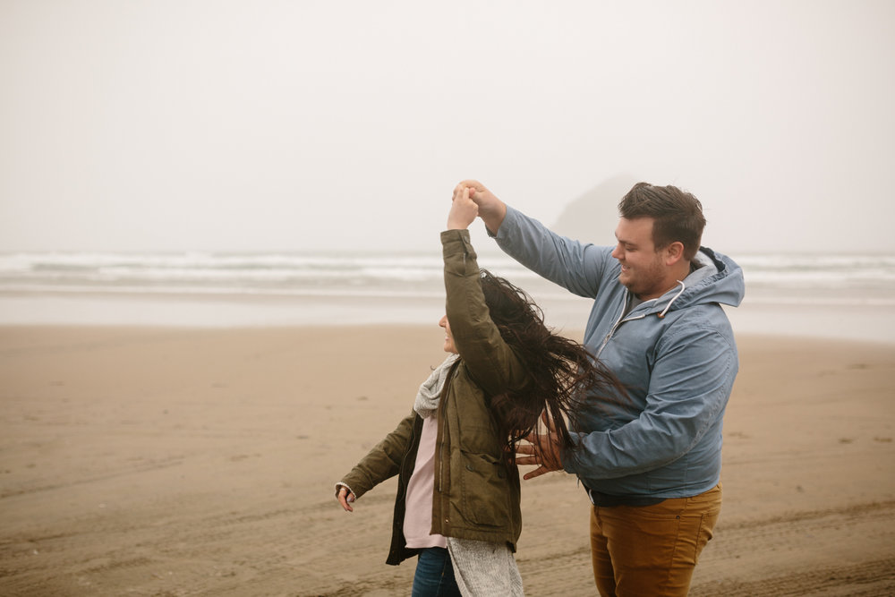 Happy young couple dancing on the beach in the wind and cold