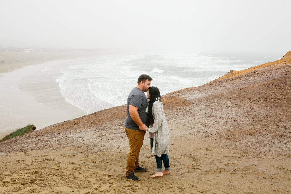 A young couple embracing while standing on a large sand dune wit