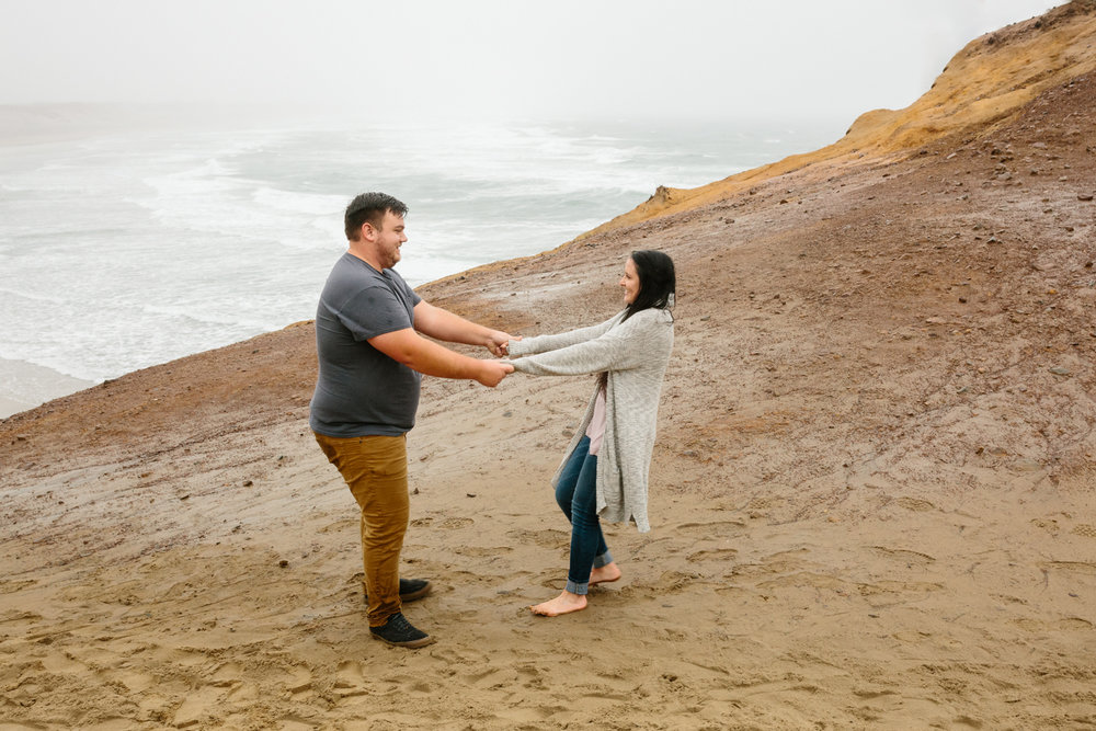 A young couple dancing while standing on a large sand dune with