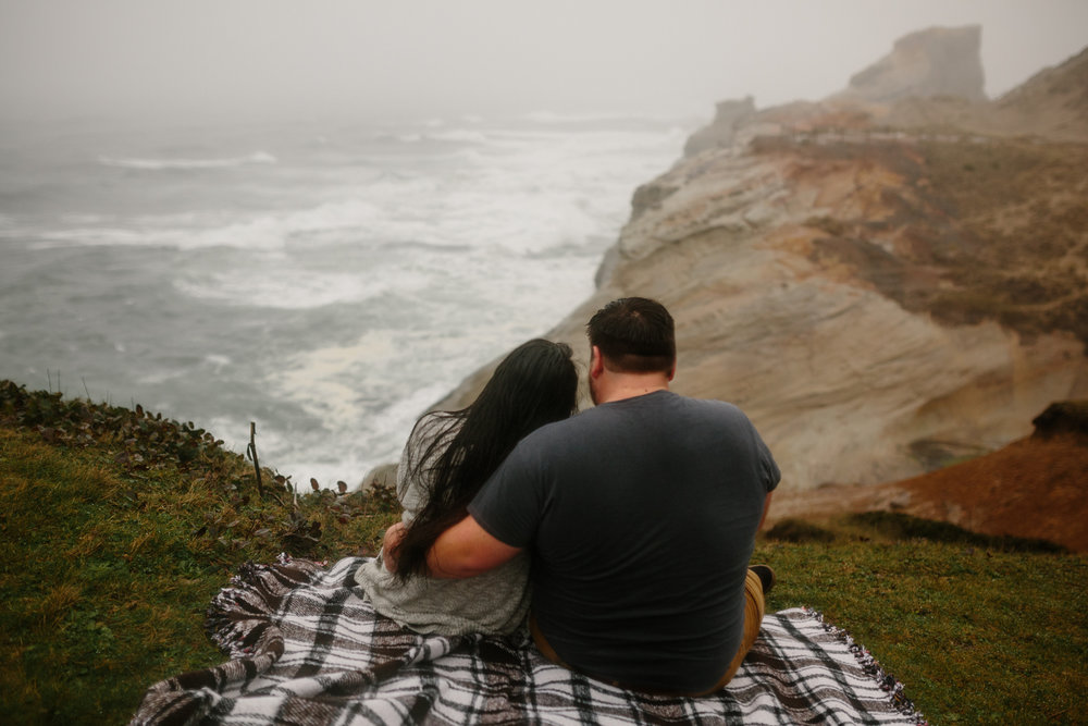 A young couple sitting on a cliff overlooking the ocean on the O