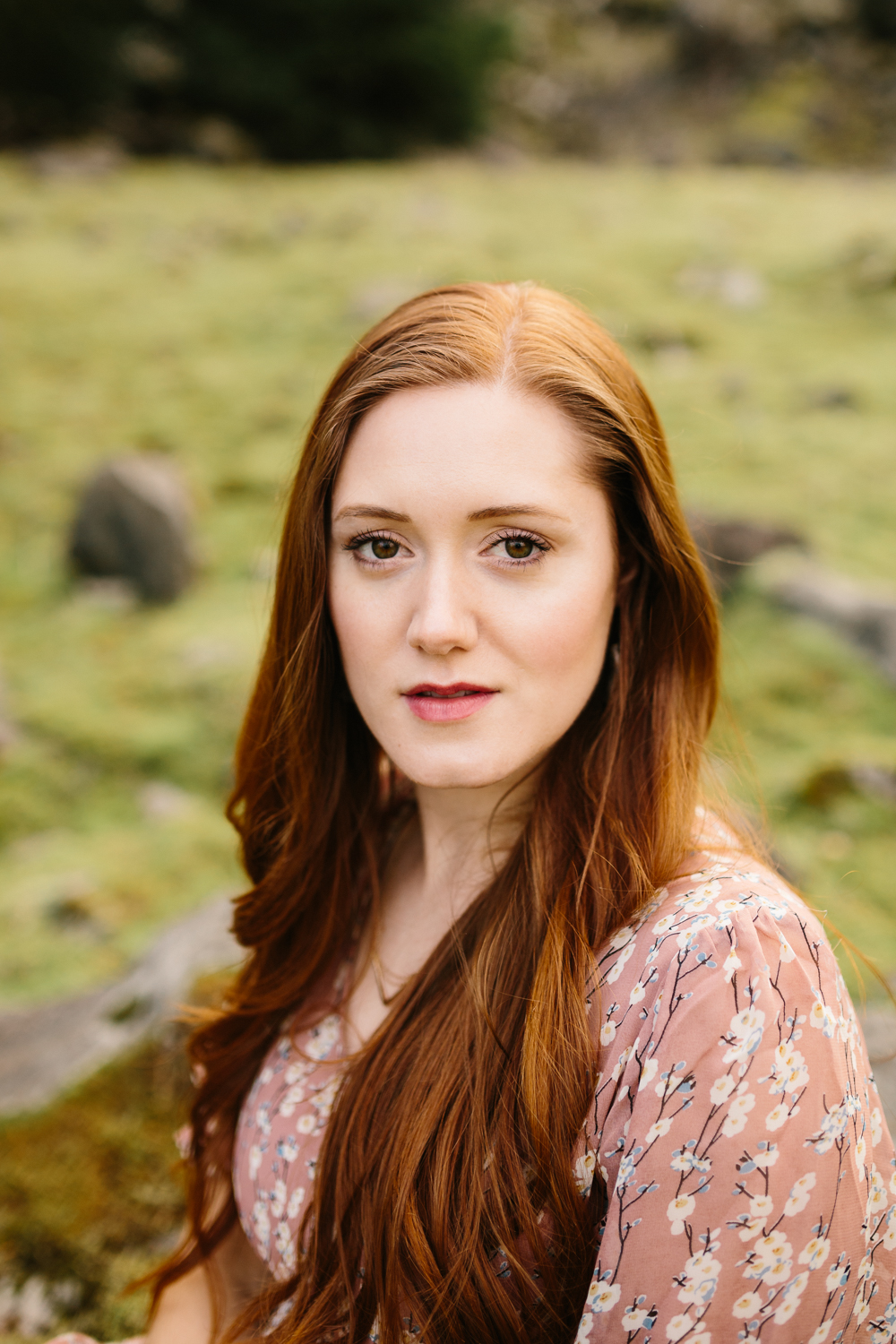 Portrait of a gorgeous red-headed woman with a mossy backdrop