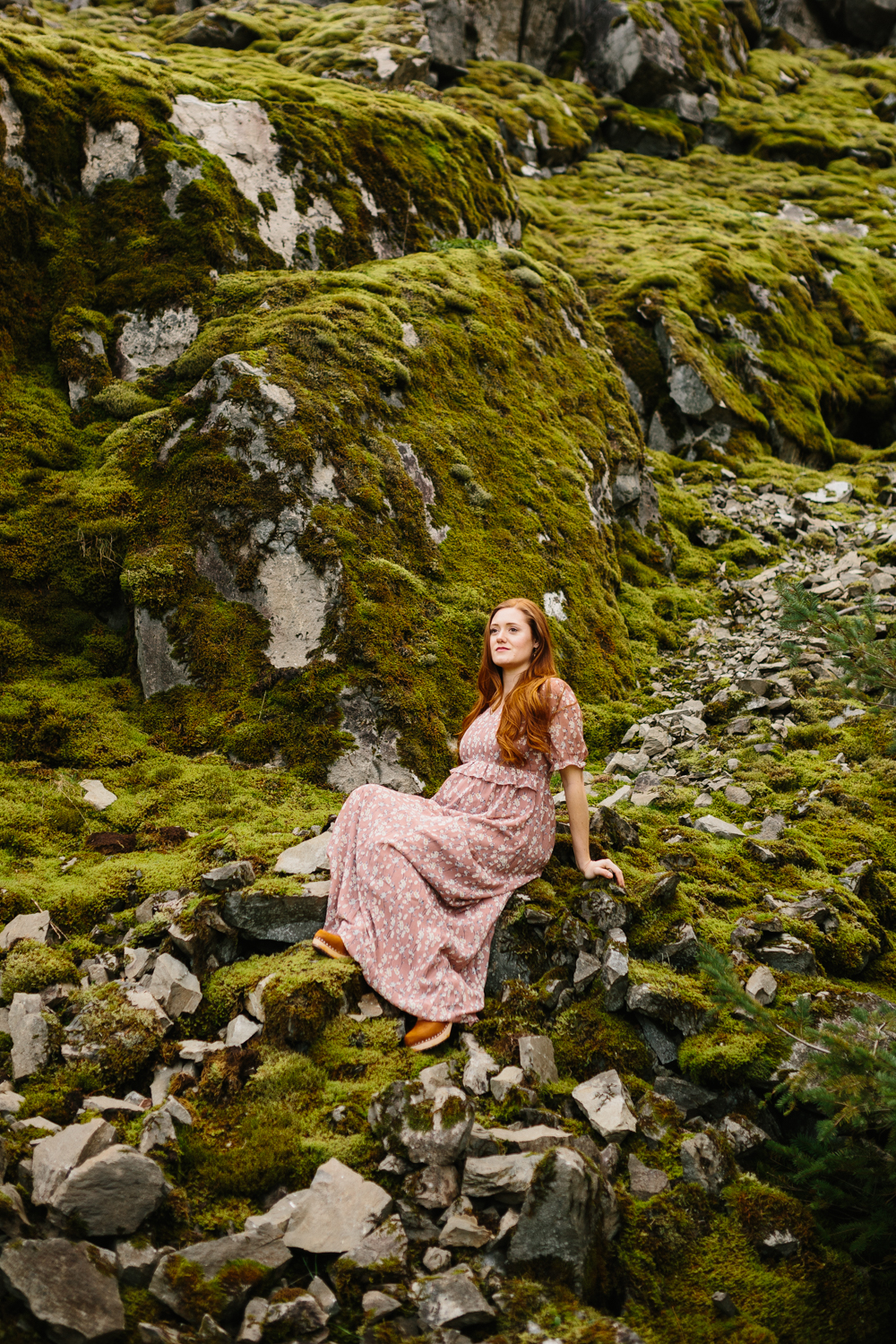 A beautiful, red-haired woman sitting on mossy rocks
