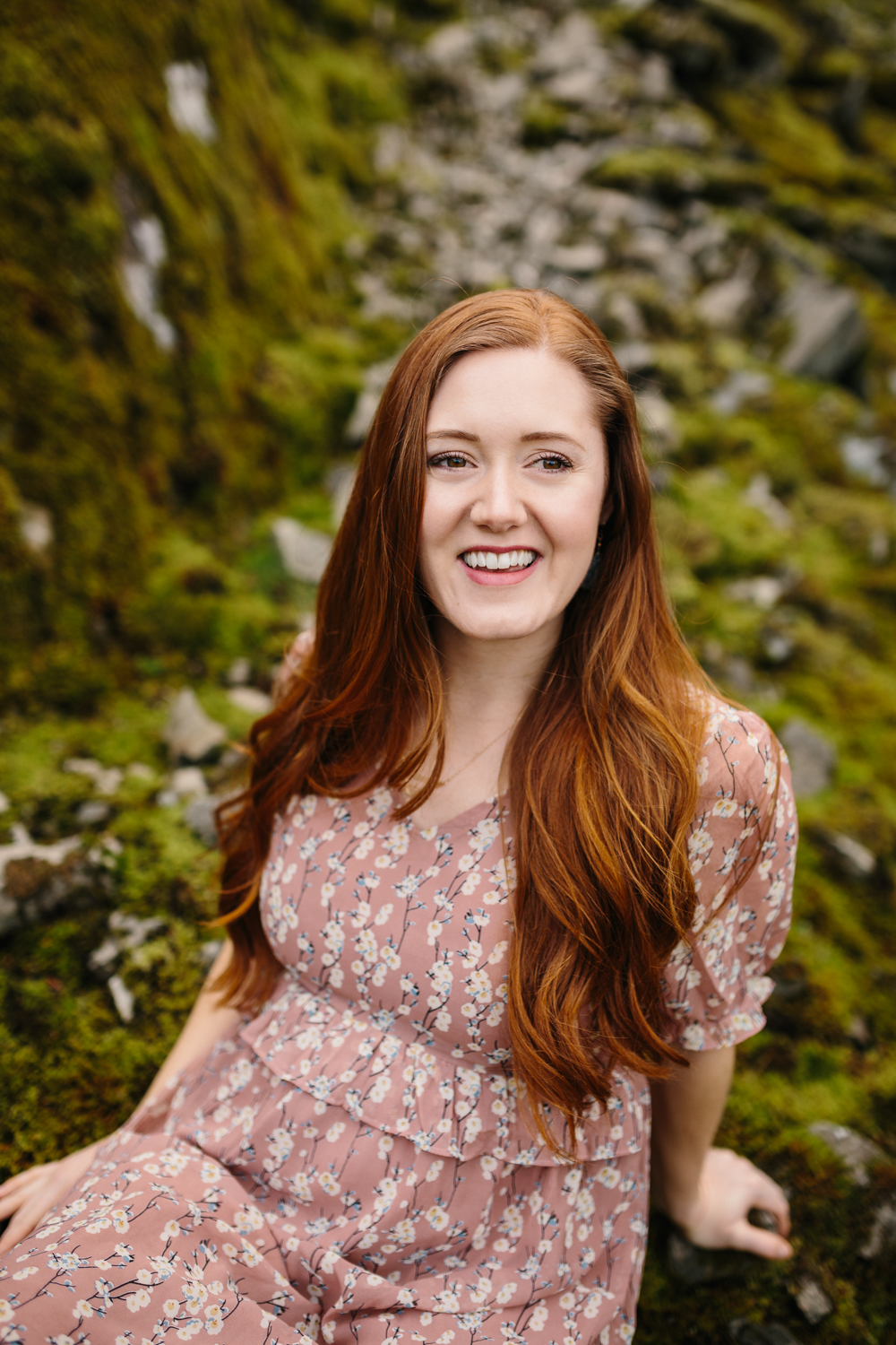 Portrait of a happy, red-haired woman sitting on mossy rocks