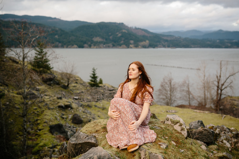 Portrait of a beautiful woman sitting on a moss covered boulder
