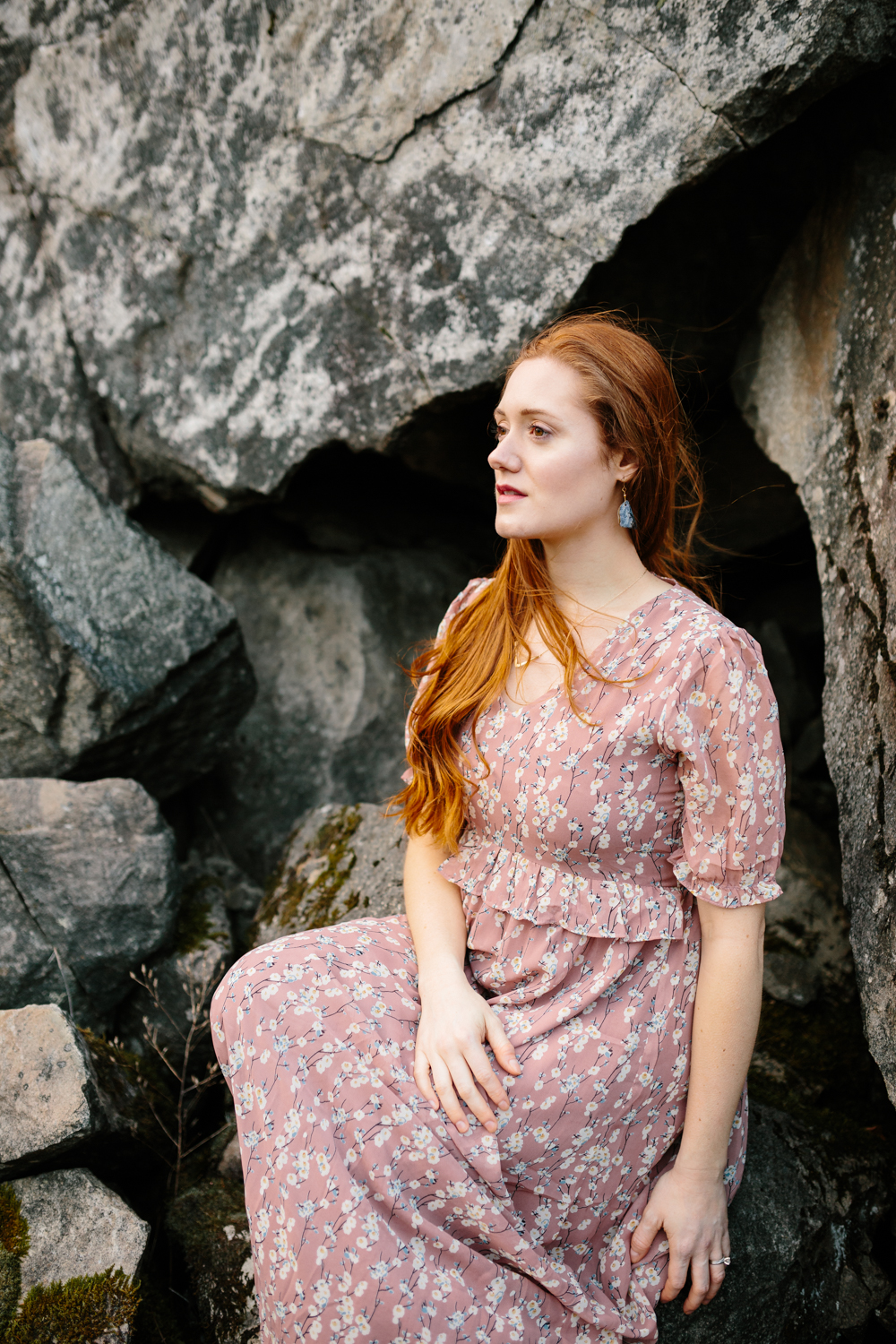 A Portrait of a Beautiful, Red-Haired Woman Sitting Amidst Bould