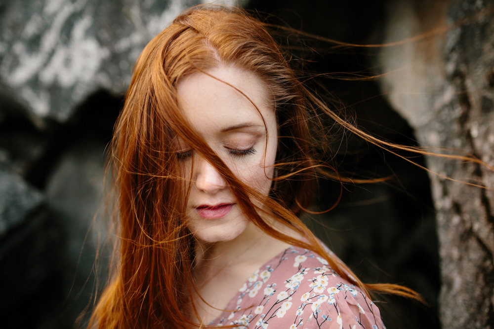 Windblown Portrait of a Beautiful, Red-Haired Woman Sitting Amid