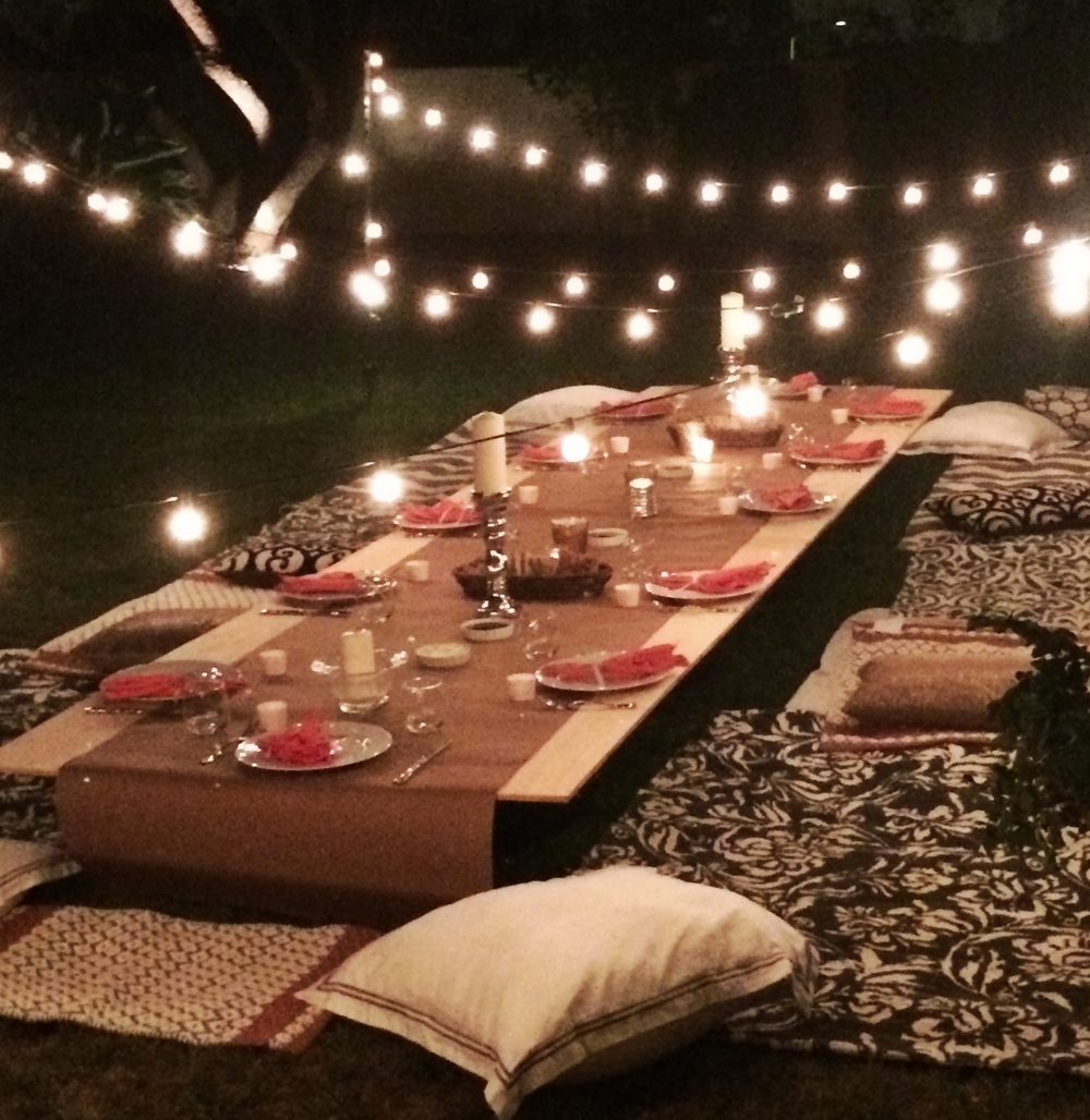 Backyard Birthday Party; white lights, plank table, rugs and pillows